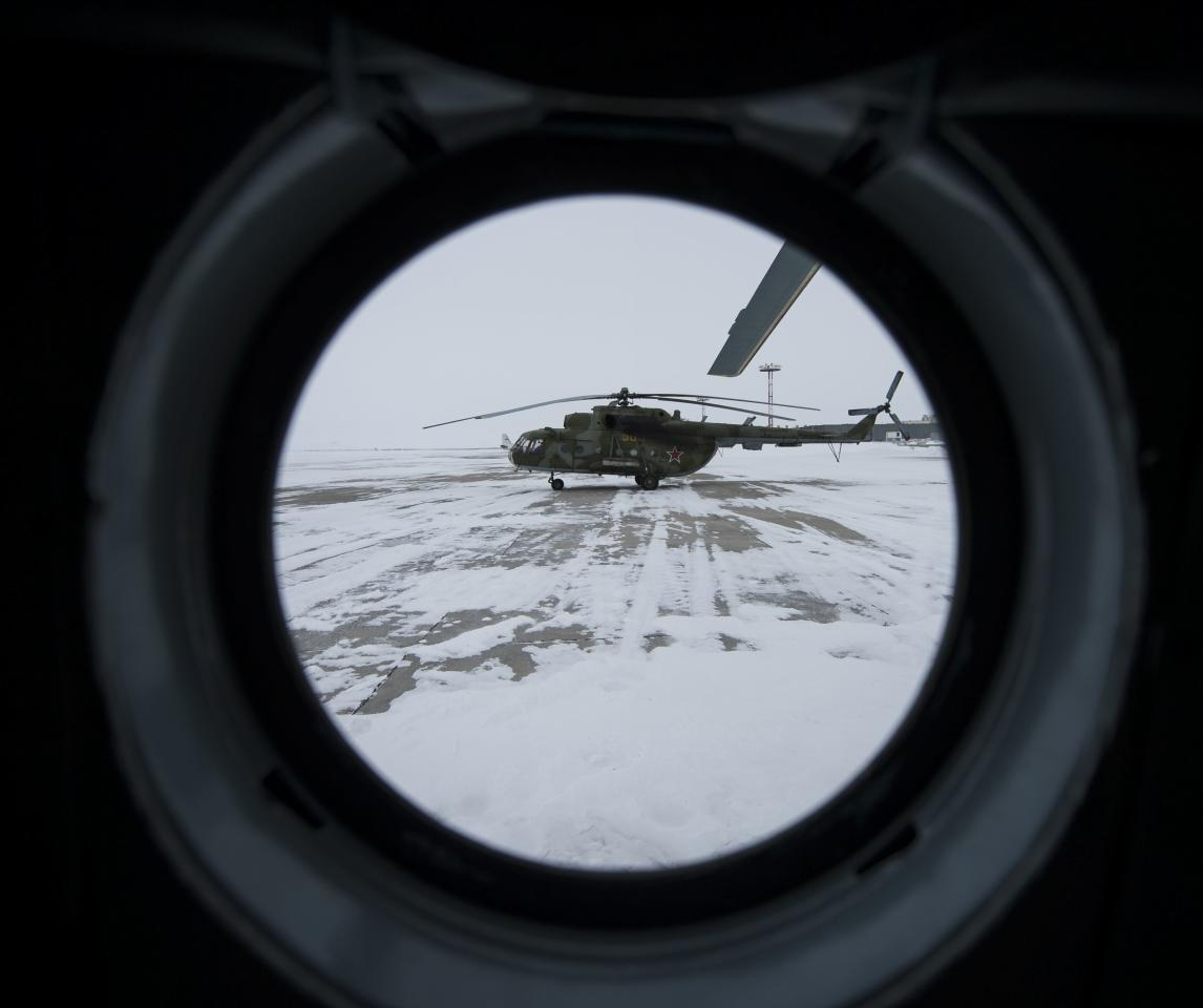 A Russian MI-8 helicopter is seen through the window of another helicopter at the Karanganda airport, March 10, 2014. Poor weather forced the fleet of 12 helicopters to turn around from their flight to Zhezkazgan, Kazakhstan where they were to have pre-staged for the landing of the Soyuz TMA-10M spacecraft carrying International Space Station (ISS) crew members, U.S. astronaut Michael Hopkins, Russian cosmonauts Oleg Kotov and Sergey Ryazanskiy, according to NASA. The ISS crew members are scheduled to land on Tuesday morning near the town of Zhezkazgan. REUTERS/Bill Ingalls/NASA/Handout via Reuters (KAZAKHSTAN - Tags: TRANSPORT SCIENCE TECHNOLOGY) ATTENTION EDITORS - THIS IMAGE HAS BEEN SUPPLIED BY A THIRD PARTY. IT IS DISTRIBUTED, EXACTLY AS RECEIVED BY REUTERS, AS A SERVICE TO CLIENTS. FOR EDITORIAL USE ONLY. NOT FOR SALE FOR MARKETING OR ADVERTISING CAMPAIGNS
