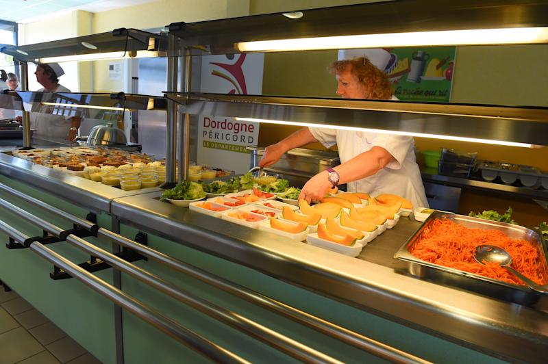 "A municipal worker displays meals before lunchtime at the canteen of the ""Pierre Fanlac"" secondary school in Belves on September 13, 2019. - This school is the first in France to receive a label ensuring that 100% of the food served at the canteen is organic. (Photo by NICOLAS TUCAT / AFP) (Photo credit should read NICOLAS TUCAT/AFP via Getty Images)"