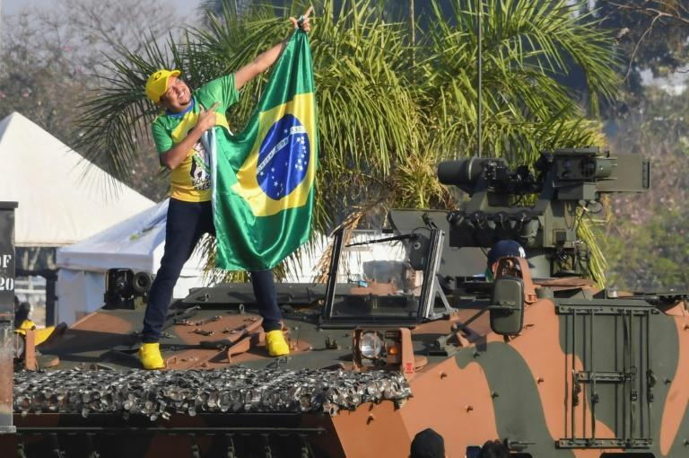 A supporter of Brazilian President Jair Bolsonaro holds a national flag while standing on a military vehicle, outside the Alvorada Palace, during the Independence Day celebrations in Brasilia (AFP/EVARISTO SA)