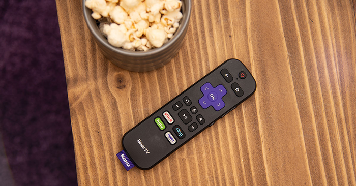 A Roku remote sitting on a table next to a bowl of popcorn