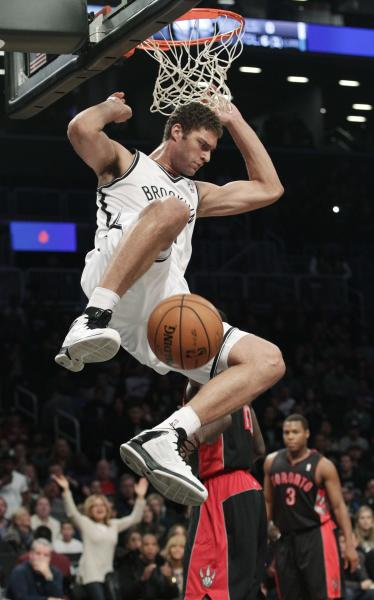 Brooklyn Nets' Brook Lopez (11) dunks the ball as Toronto Raptors' Kyle Lowry (3) looks on during the first half of an NBA basketball game, Saturday, Nov. 3, 2012, in New York. (AP Photo/Frank Franklin II)