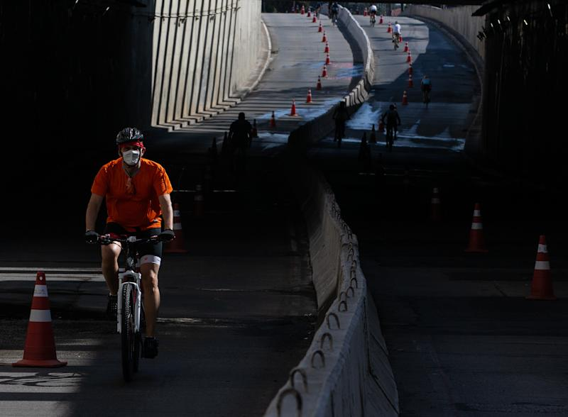 SAO PAULO, BRAZIL - JULY 19: A cyclist wearing a face mask rides in Sao Paulo's bicycle lanes amidst the coronavirus (COVID-19) pandemic on July 19, 2020 in Sao Paulo, Brazil. Leisure bike lanes in Sao Paulo returned to operation on weekends after almost a year closed. (Photo by Alexandre Schneider/Getty Images)