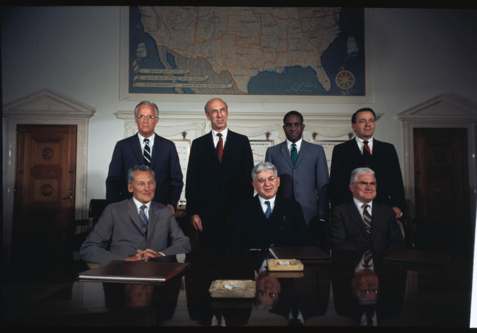 (Original Caption) Washington: Members of the Board of Governors of the Federal Reserve System pose for the first time since Arthur Burns replaced Wm. McC Martin as chairman. Groupings are as follows: Foreground: Chairman Arthur Burns; background (l to r): J.L. Robertson, vice chairman; Sherman J. Maisel; J. Dewey Daane; Andrew F. Brimmer; George Mitchell; and Mitchell W. Sherrill.