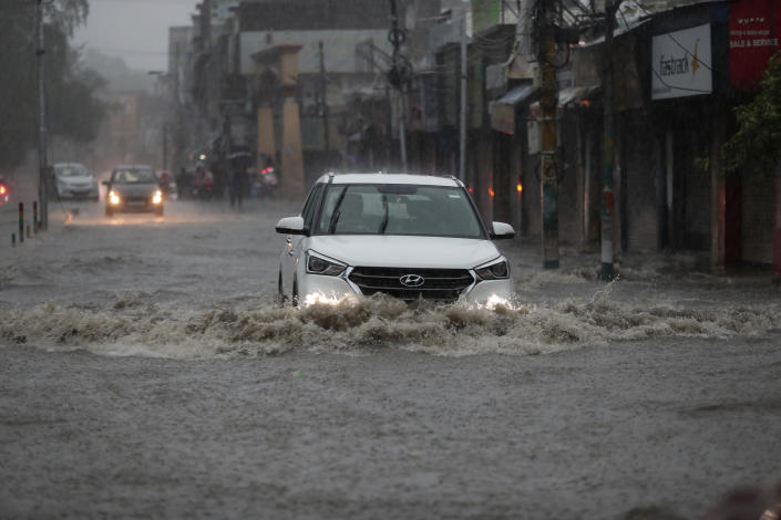 A car moves through a flooded street during monsoon rains Jammu, India, Monday, July 12, 2021. India's monsoon season runs from June to September. (AP Photo/Channi Anand)