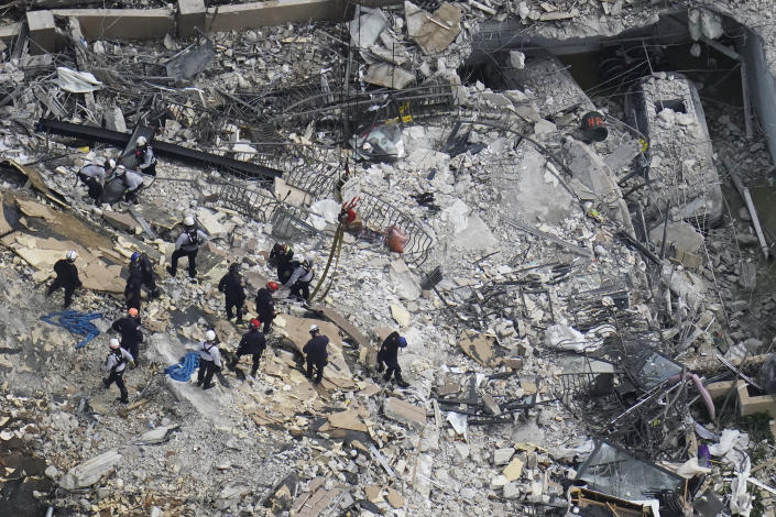 Image: Rescue workers search in the rubble at the Champlain Towers South Condo, in Surfside, Fla., on June 26, 2021. (Gerald Herbert / AP)