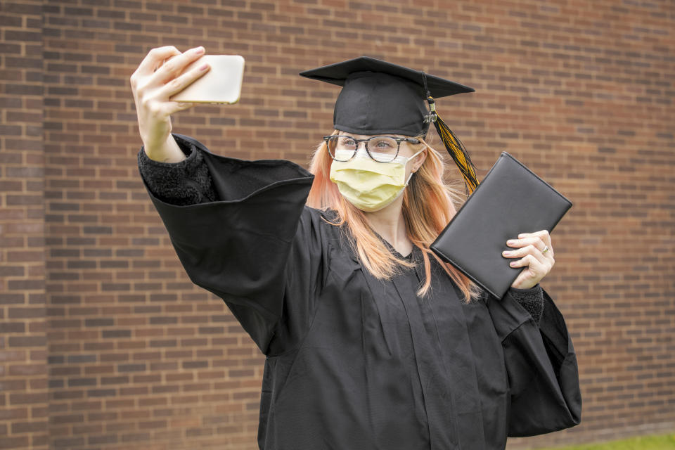 A high school graduate of the class of 2020 takes a selfie on her cell phone in her cap and gown holding a diploma as she wears a face mask.
