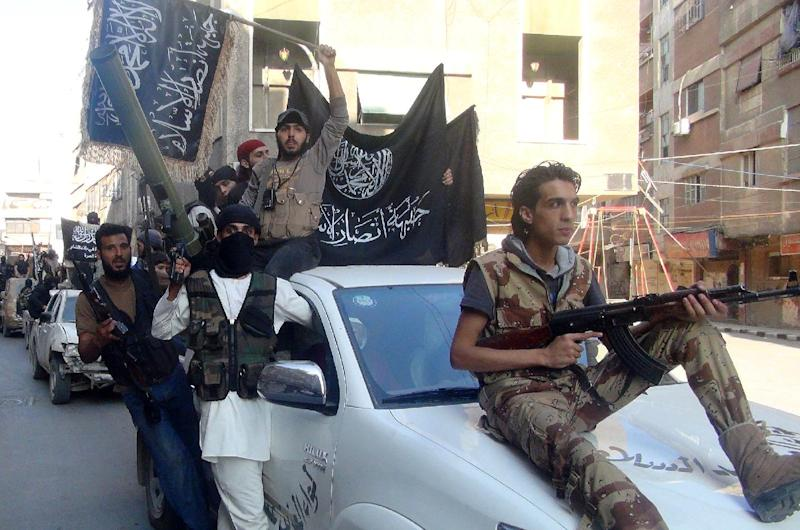 Islamic fighters from the Al-Nusra Front wave their movement's flag as they parade at the Yarmuk Palestinian refugee camp, south of Damascus on July 28, 2014