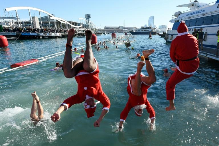 Participants jump into the water during the 110th edition of the 'Copa Nadal' (Christmas Cup) swimming competition in Barcelona's Port Vell (AFP Photo/Josep LAGO)