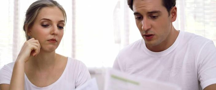 Young couple looking at their housing expenses.