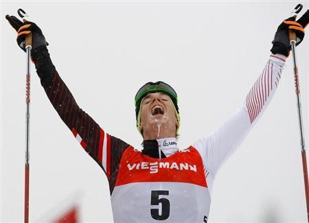 Duerr celebrates as he crosses the finish line to third place during the men's FIS World Cup cross-country skiing 9km free final climb pursuit race on the Alpe Cermis in Val di Fiemme