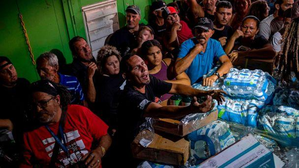 PHOTO: People break into a warehouse with supplies believed to have been from when Hurricane Maria struck the island in 2017 in Ponce, Puerto Rico on Jan. 18, 2020. (Ricardo Arduengo/AFP via Getty Images)