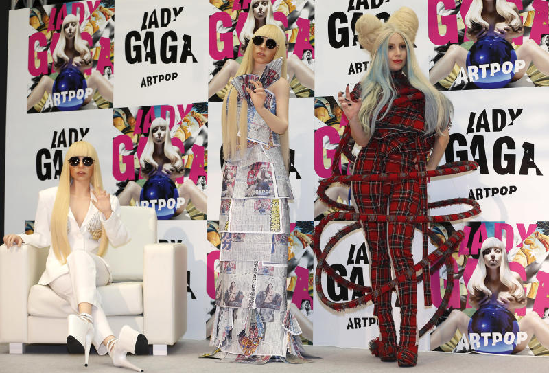"""Lady Gaga poses for photographers with her life-sized dolls during a press conference to promote her album """"ARTPOP"""" in Tokyo, Sunday, Dec. 1, 2013. (AP Photo/Shizuo Kambayashi)"""