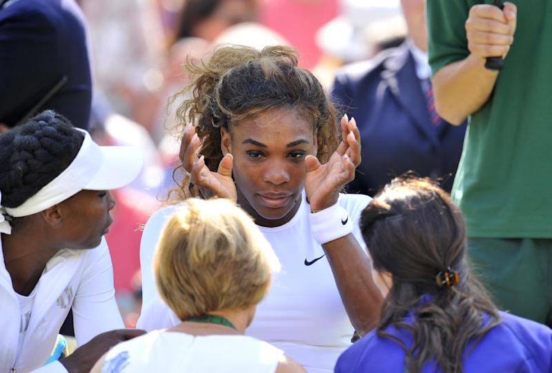US player Serena Williams (C) wipes her eyes after being taken ill as her partner Venus Williams (L) looks on during their second round doubles match at the 2014 Wimbledon Championships in Wimbledon, southwest London, on July 1, 2014