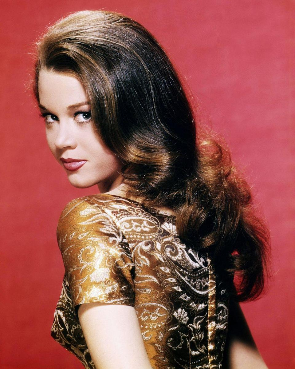 <p>Here, Fonda looks over her shoulder for a photograph, showing off a longer, darker hairstyle.</p>