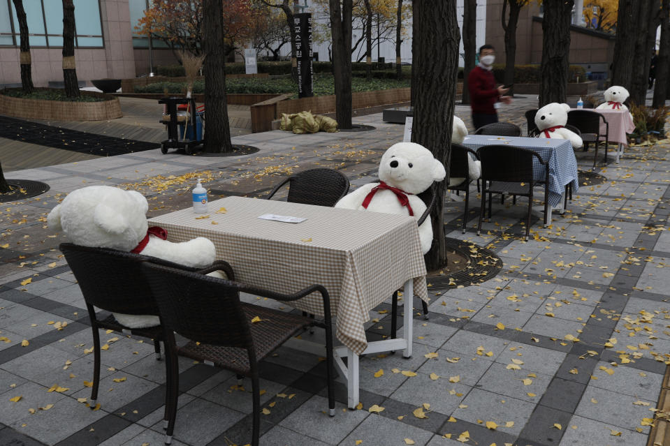Tables and chairs are placed with hand sanitizers and stuffed toys while maintaining social distancing in downtown Seoul, South Korea, Wednesday, Nov. 18, 2020. This is one of the programs for a week, for the people who are tired from COVID-19, can enjoy while maintaining social distancing and for downtown revitalization. (AP Photo/Lee Jin-man)