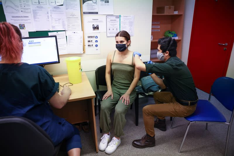 A person receives a dose of the Pfizer BioNTech vaccine, at vaccination centre for young people and students at the Hunter Street Health Centre, amid the coronavirus disease (COVID-19) outbreak, in London