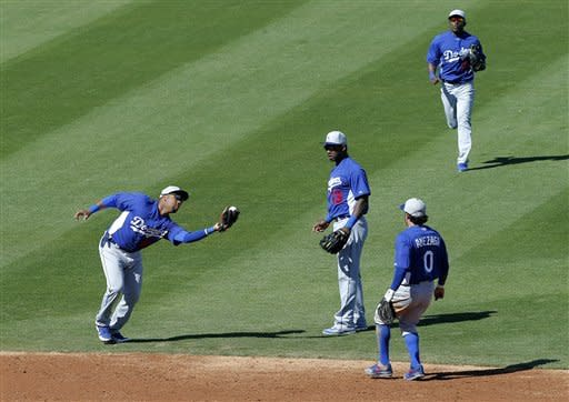 Los Angeles Dodgers' Omar Luna, left, catches a fly ball as teammate Hanley Ramirez (13), Alfredo Amezaga (0) and Elian Herrera watch during the second inning of a spring training baseball game against the Chicago Cubs, Wednesday, Feb. 27, 2013, in Mesa, Ariz. (AP Photo/Matt York)