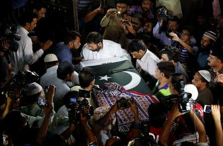Relatives carry the casket, wrapped in national flag and shawl, locally known as Ajrak, containing the body of Sabika Aziz Sheikh, in Karachi,