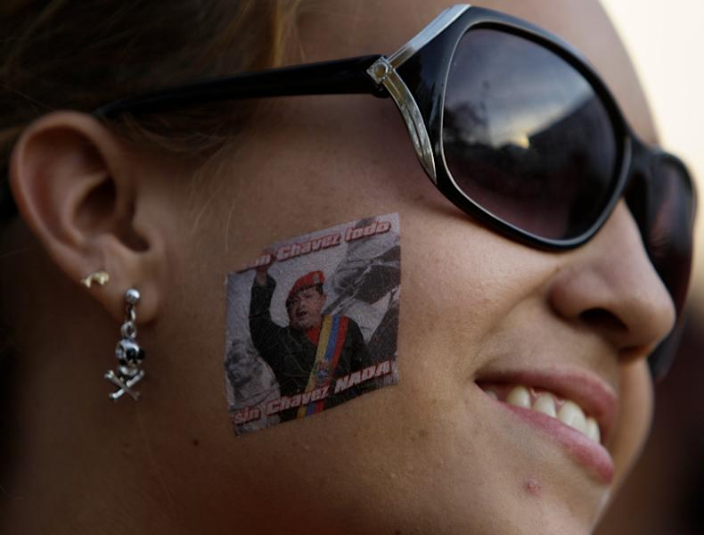 A supporter of Venezuela's President Hugo Chavez wears a sticker with an image of him as she waits in line outside the military academy to see the body of Chavez lying in state in Caracas, Venezuela, Thursday, March 7, 2013. While Venezuela remains deeply divided over the country's future, the multitudes who reached the president's coffin were united in grief and admiration for a man many considered a father figure. Chavez died on March 5 after a nearly two-year bout with cancer. (AP Photo/Fernando Llano)