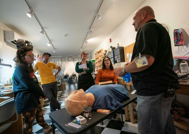 Elvis Rosado (R), of the association Prevention Point, trains the employees of Souvenir Jewelry in Philadelphia in how to administer naloxone, which reverses the effects of an opioid overdose