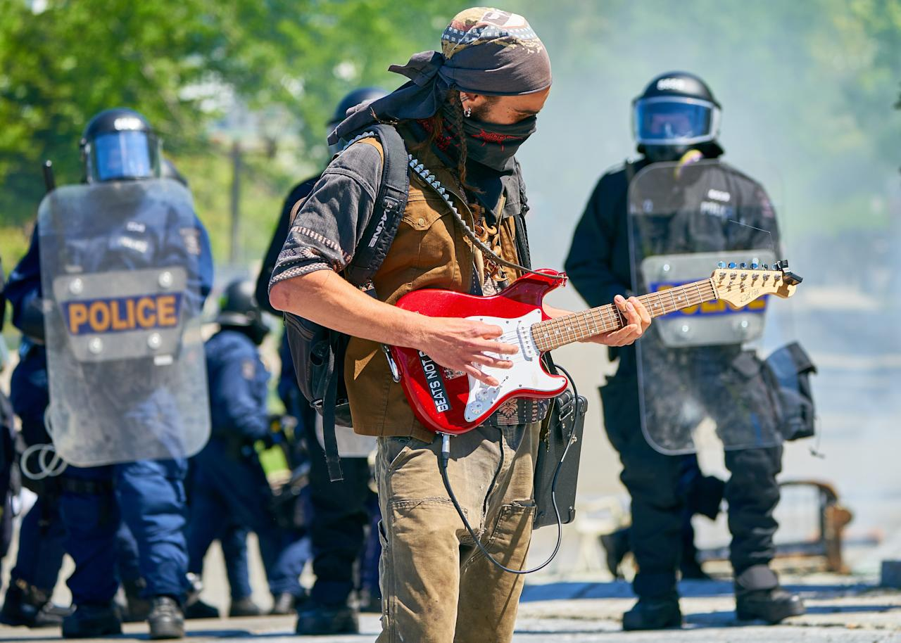 <p>Protester play guitar in front of anti riot police in the middle of the street during protests against the G7 Summit in Quebec City. EPA/ANDRE PICHETTE </p>