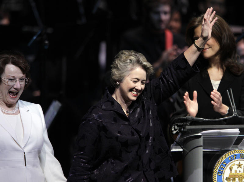 FILE - In this Monday, Jan. 4, 2010 file photo, Houston Mayor Annise Parker, center, walks onto the stage with her partner, Kathy Hubbard, during her public inauguration ceremony in Houston. Houston is the largest U.S. city to elect an openly gay mayor. (AP Photo/David J. Phillip)