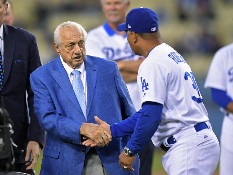 Former Dodgers manager Tommy Lasorda shakes hand with current manager Dave Roberts during a ceremony in honor of Lasorda's 90th birthday. (AP)