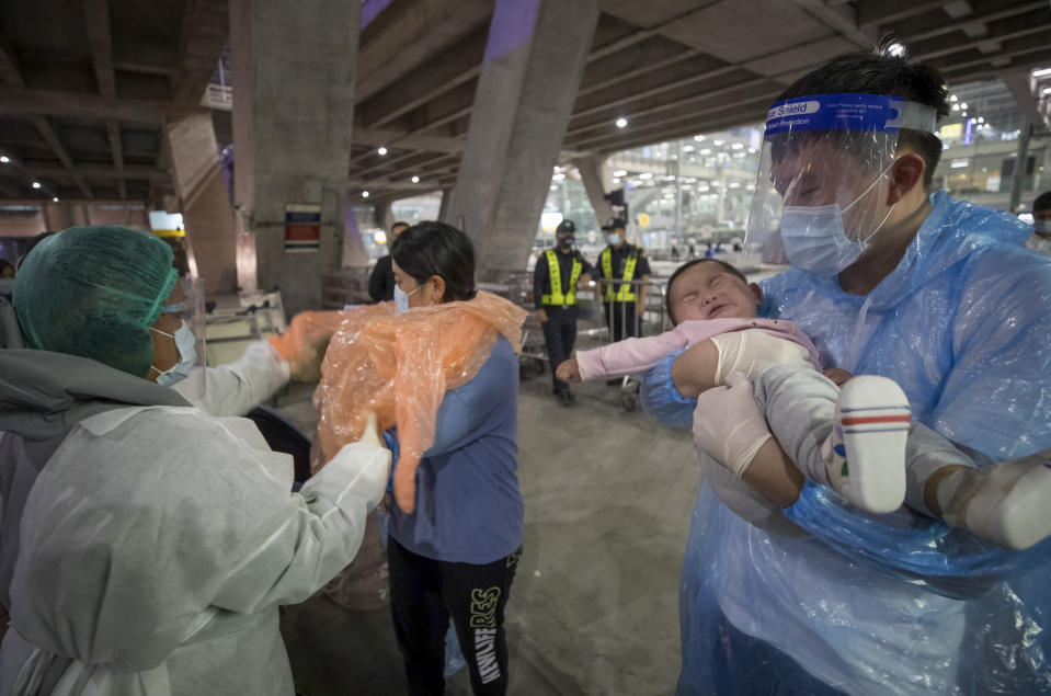 A public health worker helps chinese tourists, who arrived at Suvarnabhumi airport on special tourist visas, in Bangkok, Thailand, Tuesday, Oct. 20, 2020. Thailand on Tuesday took a modest step toward reviving its coronavirus-battered tourist industry by welcoming 39 visitors who flew in from Shanghai, the first such arrival since normal traveler arrivals were banned almost seven months ago. (AP Photo/Wason Wanichakorn)