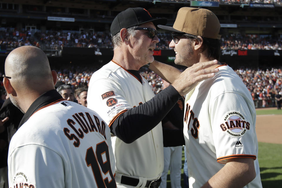 San Francisco Giants manager Bruce Bochy, center, hugs former player Barry Zito during a ceremony honoring Bochy after a baseball game between the Giants and the Los Angeles Dodgers in San Francisco, Sunday, Sept. 29, 2019. (AP Photo/Jeff Chiu, Pool)