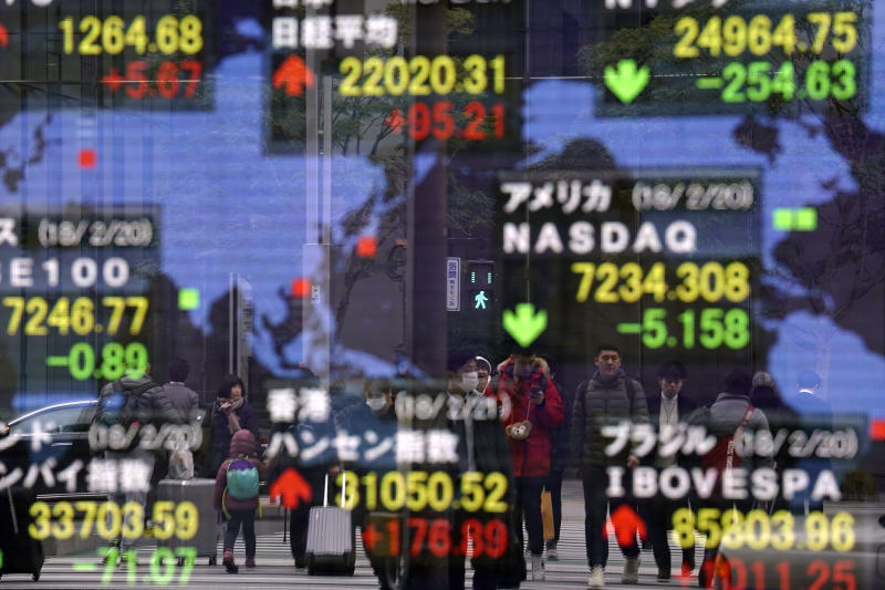 People are reflected on an electronic stock indicator of a securities firm in Tokyo, Wednesday, Feb. 21, 2018. Shares were higher in Asia on Wednesday, supported by rosy manufacturing data from Japan. The gains came despite losses on Wall Street, where a six-day winning streak was snapped by a plunge in Walmart stock and losses in other sectors. (AP Photo/Shizuo Kambayashi)