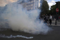 Demonstrators kick in tear gas grenades fired by police forces during a banned protest in support of Palestinians in the Gaza Strip, Saturday, May, 15, 2021 in Paris. Marches in support of Palestinians in the Gaza Strip were being held Saturday in a dozen French cities, but the focus was on Paris, where riot police got ready as organizers said they would defy a ban on the protest. (AP Photo/Michel Euler)