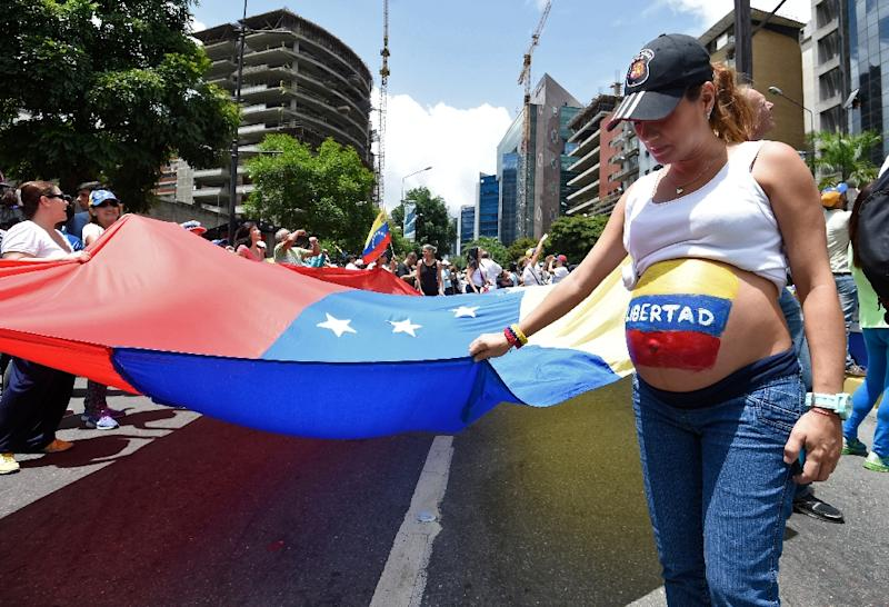 "A pregnant opposition activist with the word ""Freedom"" written on her belly takes part in a demonstration marking 100 days of protests against Venezuelan President Nicolas Maduro in Caracas, on July 9, 2017 (AFP Photo/Juan BARRETO)"