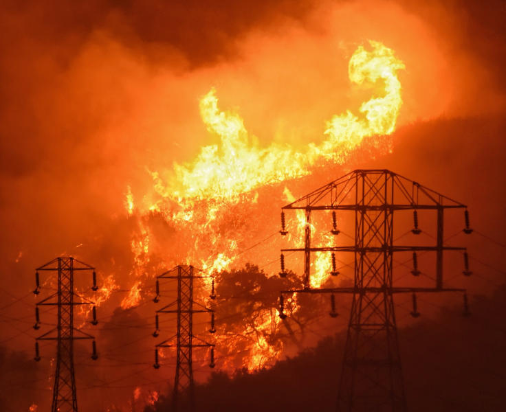 FILE - In this Dec. 16, 2017, file photo provided by the Santa Barbara County Fire Department, flames burn near power lines in Sycamore Canyon near West Mountain Drive in Montecito, Calif.  Pacific Gas & Electric said it will shut off power Saturday, June 8, to about 1,600 customers in Northern California and may do the same for thousands more to reduce the risk of wildfires. The utility announced Friday night that as of Saturday morning it will turn off electricity to customers in Napa, Solano and Yolo counties west of Sacramento.  (Mike Eliason/Santa Barbara County Fire Department via AP, File)