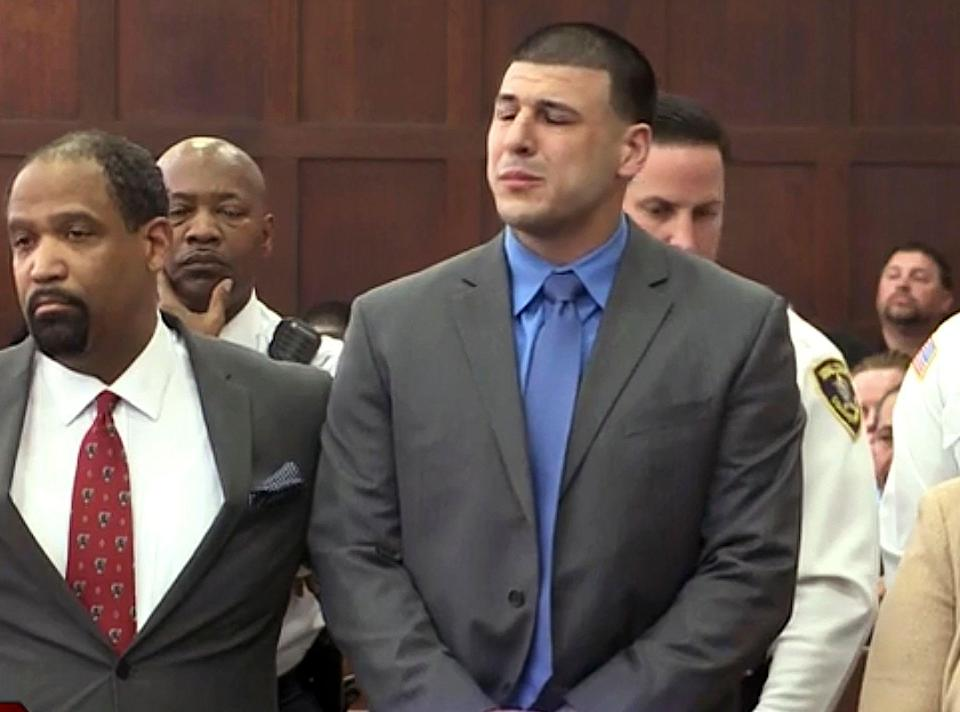 In this still image from video, Aaron Hernandez, right, listens beside defense attorney Ronald Sullivan, Friday, April 14, 2017, in court in Boston, as he is pronounced not guilty of murder in the 2012 shootings of two men in a drive-by shooting in Boston. (WHDH-TV via AP, Pool)