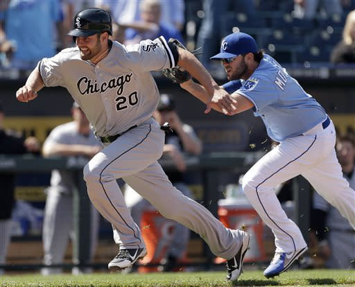 Chicago White Sox's Jordan Danks (20) is caught in a rundown by Kansas City Royals third baseman Mike Moustakas to end the ninth inning of a baseball game, Monday, May 6, 2013, in Kansas City, Mo. The White Sox won 2-1 in 11 innings. (AP Photo/Charlie Riedel)