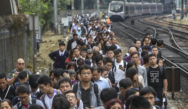 Commuters walk on the tracks near Sha Tin MTR station after train services are disrupted. Photo: Winson Wong
