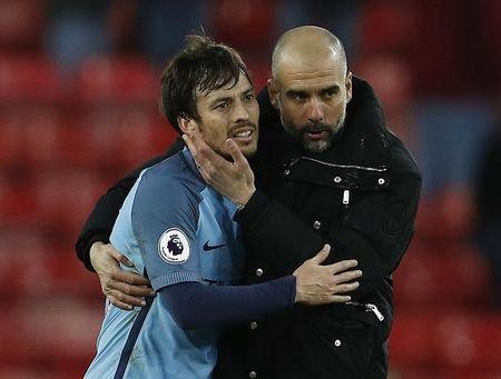 Manchester City manager Pep Guardiola celebrates with David Silva after the match