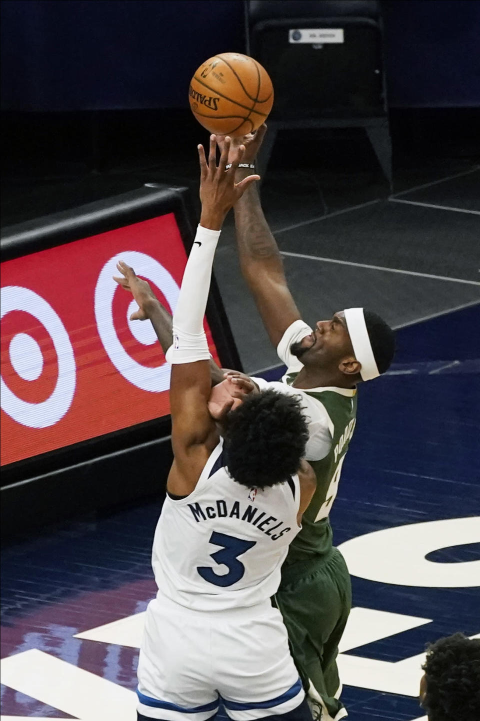 Milwaukee Bucks' Bobby Portis (9) shoots over Minnesota Timberwolves' Jaden McDaniels (3) in the first half of an NBA basketball game Wednesday, April 14, 2021, in Minneapolis. (AP Photo/Jim Mone)