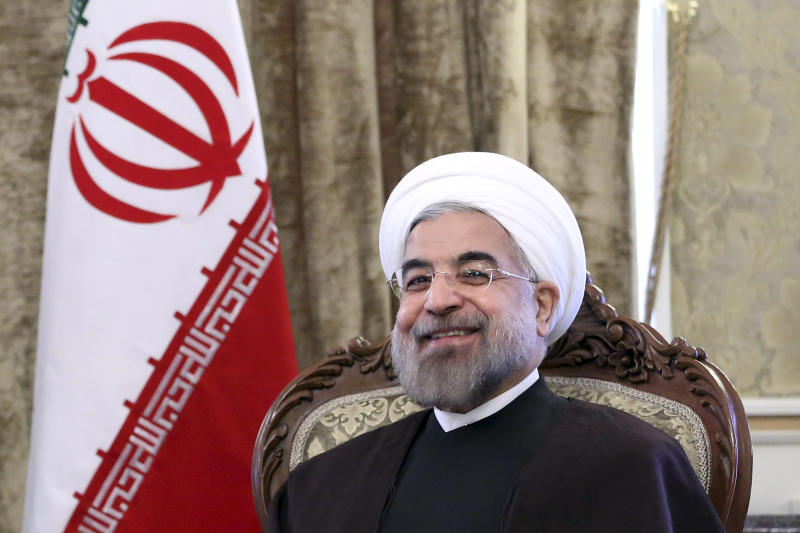 Iran's President Hassan Rouhani, smiles during a meeting with Afghan President Hamid Karzai, at Tehran's Saadabad Palace in Iran, Sunday, Dec. 8, 2013. Karzai arrived in Tehran for a one-day visit on Sunday to discuss regional and international issues with Iranian officials. (AP Photo/Ebrahim Noroozi)