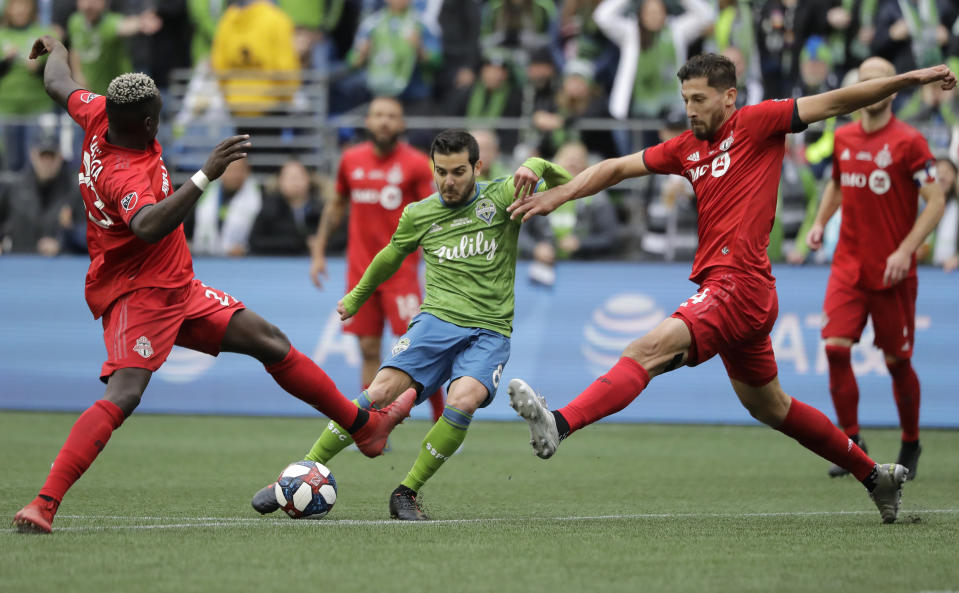 Seattle Sounders' Victor Rodriguez, center, kicks the ball to score between Toronto FC's Chris Mavinga, left, and Omar Gonzalez, Sunday, Nov. 10, 2019, during the second half of the MLS Cup championship soccer match in Seattle. (AP Photo/Ted S. Warren)