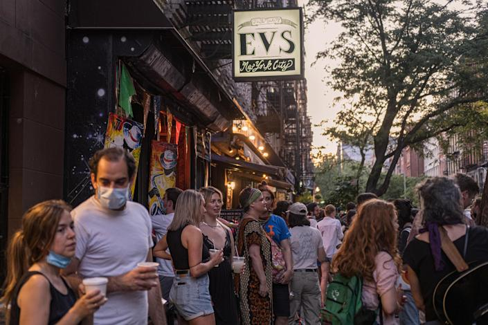 People drink outside a bar during the reopening phase following the coronavirus disease (COVID-19) outbreak in the East Village neighborhood in New York U.S., June 12, 2020. Picture taken June 12, 2020. REUTERS/Jeenah Moon