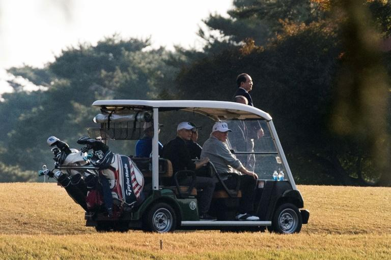 US President Donald Trump (front R) and Japanese Prime Minister Shinzo Abe (front L) return in a golf cart after playing a round