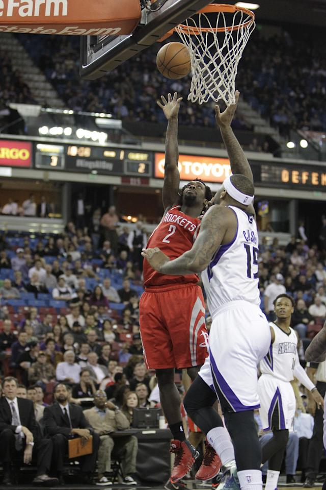 Houston Rockets guard Patrick Beverly, left, shoots against Sacramento Kings center DeMarcus Cousins during the first quarter of an NBA basketball game in Sacramento, Calif., Tuesday Feb. 25, 2014. (AP Photo/Rich Pedroncelli)
