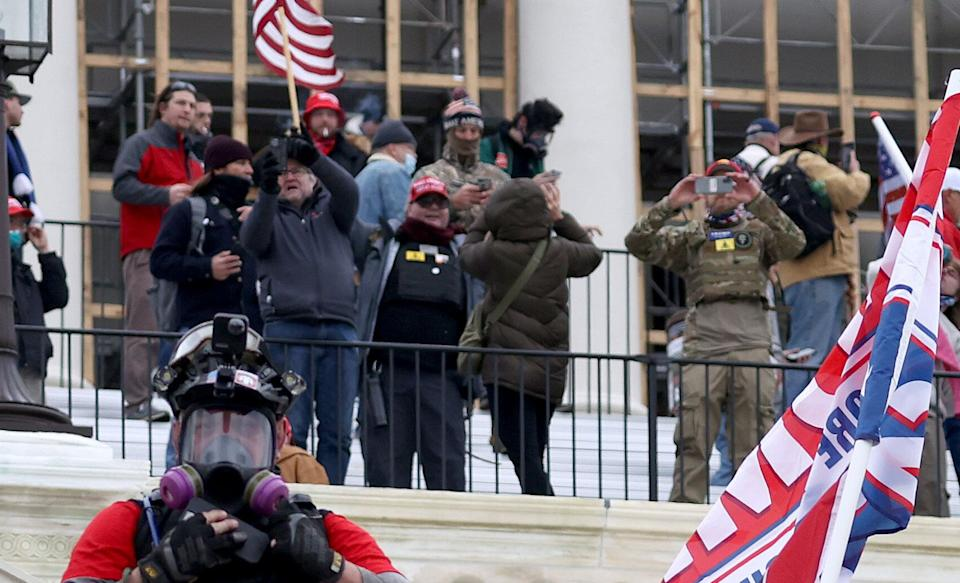 Russ Taylor (middle, in MAGA hat) on the west side of the Capitol during the attack. Another likely defendant, wearing a similar patch, appears on the right. (Photo: Tasos Katopodis via Getty Images)