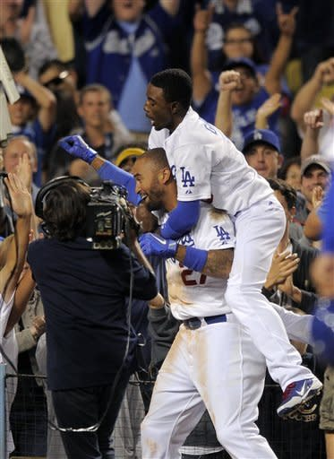 Los Angeles Dodgers' Dee Gordon, right, jumps on the back of Matt Kemp after Kemp hit a walk-off home run in the tenth inning of their baseball game against the Washington Nationals, Saturday, April 28, 2012, in Los Angeles. The Dodgers won 4-3. (AP Photo/Mark J. Terrill)
