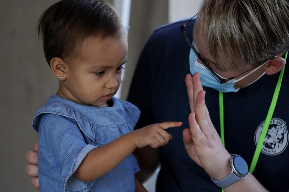 Volunteer Mark McDonald, right, works with a young immigrant at a clinic set up for asylum seekers waiting in Matamoros, Mexico, Thursday, Nov. 19, 2020. A humanitarian organization led by U.S. military veterans has treated thousands of migrants over the past year at two clinics in a Mexican town across the border from Texas. But Global Response Management is attempting to go beyond mere crisis response and build a system to make it easier to track the health of migrants along their journey from Central America. The efforts are part of a growing trend in humanitarian aid that has accelerated amid the coronavirus pandemic, which has highlighted the difficulties of getting basic health care to migrants. (AP Photo/Eric Gay)