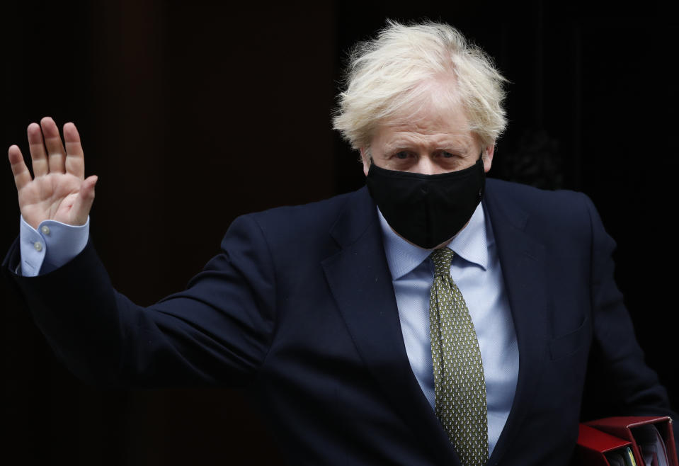 Britain's Prime Minister Boris Johnson waves as he leaves 10 Downing Street for the House of Commons for his weekly Prime Minister's Questions in London, Wednesday, Oct. 14, 2020. (AP Photo/Alastair Grant)