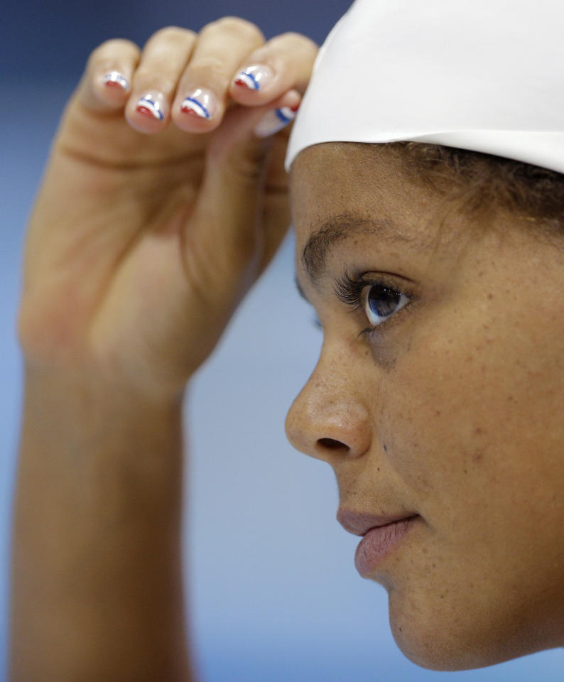 Coralie Balmy of France wears nail polish in the colors of the French flag as she trains at the Aquatics Center at the Olympic Park ahead of the 2012 Summer Olympics, Wednesday, July 25, 2012, in London. Opening ceremonies for the 2012 London Olympics will be held Friday, July 27.(AP Photo/Michael Sohn)