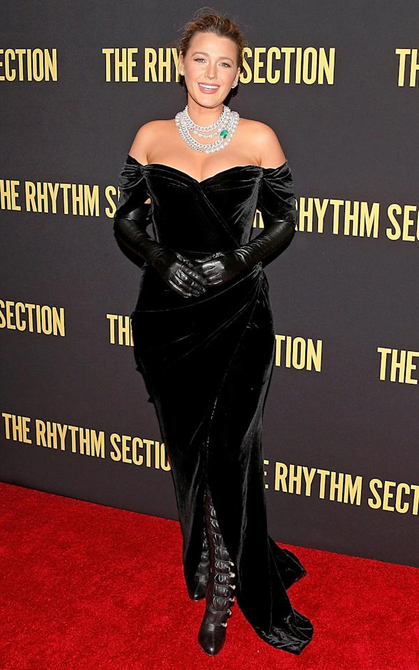 wears a black velvet off-the-shoulder Dolce & Gabbana gown, leather opera gloves, black leather over-the-knee Christian Louboutin boots with button detail and aLorraine Schwartz necklace at the <em>The Rhythm Section</em> screening in Brooklyn.