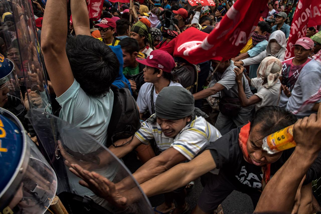<p>Protesters push their way through a phalanx of riot police a day ahead of President Trump's arrival on Nov. 11, 2017 in Manila, Philippines. (Photo: Jes Aznar/Getty Images) </p>